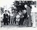 Mayor John F. Collins holding fishing pole with daughter Margaret at his side as unidentified group of men and children look on at Jamaica Pond (10290660566).jpg
