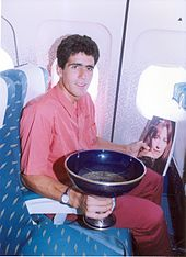 A man sitting in a blue seat, holding a trophy and a magazine