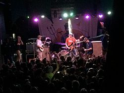 Image of a concert with an audience and the band Modern Baseball both shown
