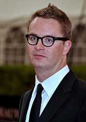 A photograph of filmmaker Nicholas Winding Refn, wearing glasses and suit with bow tie.
