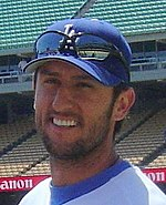 a smiling man with a LA Baseball cap and sunglasses above the caps visor smiles while wearing a stubble beard.