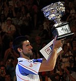 A brown-haired man in a white tennis shirt with light blue sections and red stripes with the trophy