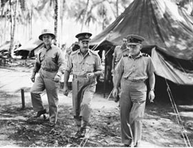 Three men in light-coloured military uniforms walking from tent, with palm trees in background
