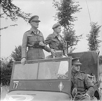 John Crocker - Lieutenant General John Crocker watching the fighting near Caen from a jeep, July 1944. With him are his aide-de-camp, Captain Cross, and Lance Corporal Marsden, his driver.