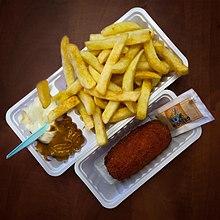 Tipico cibo da strada: patate fritte con maionese e pindasaus accompagnata da una kroket con una bustina senape