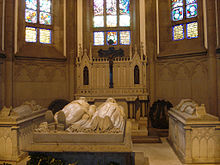 Inside a gothic chapel, a marble effigy of a bearded emperor in uniform and his wife lies atop an intricately carved stone sarcophagus