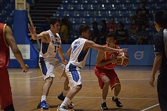 Malaysia national basketball team - A Malaysian player guarding the ball from two Filipino players.