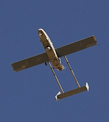 A large airborne machine photographed in flight from the ground looking up. The machine is pointed toward the top left side of the photo. Large wings can be seen protruding from the vehicle, along with the tail fin and metal peinces that attach it to the body of the aircraft. Visible in the machine's underbelly are a camera and landing gear, tail hook, and a blur in the back where a small propeller responsible for powering the machine can be found.