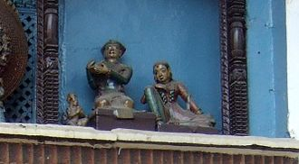 Pratap Malla - Pratap Malla, playing a lute, and his queen, seen in the niche above the Hanuman Dhoka Palace gate.