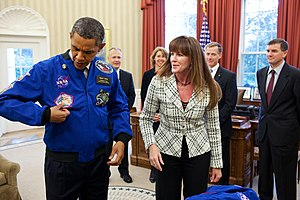 STS-135 - The crew presents President Obama with a coat from the final mission.