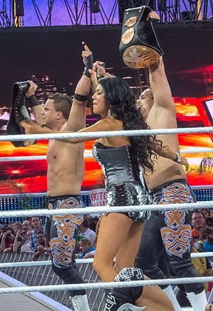 Epico Colón - Epico (right) and Primo (left) as the WWE Tag Team Champions, accompanied by  Rosa Mendes (center).