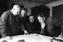 Foto av flere menn i uniform som undersøker et kart som ligger på et bord