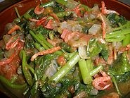 Closeup of stewed green leaves, tomato and tiny shrimp