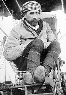 A black and white photograph of Roger Sommer, a man with a short beard, sitting in a Farman biplane seat surrounded by wires