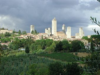 View of a small town on a hilltop surrounded by trees and vineyards. There are eight tall square towers rising from among the densely packed houses.