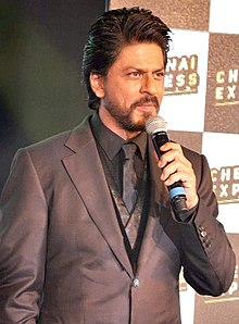 Shah Rukh Khan with a beard, wearing a full suit and holding a microphone in 2013