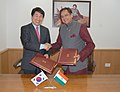 Shashi Tharoor and the Minister of Education, Science and Technology, Republic of Korea, Dr. Lee Ju-Ho exchanging the signed documents of a Memorandum of Understanding on Educational Cooperation between the two countries.jpg