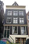 foto van Huis met gevel onder 19e-eeuwse rechte lijst waarboven een stenen punttopje uitsteekt