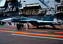 Aqua and blue jet aircraft on aircraft carrier deck, with a group of men standing close-by. Behind the jet is the ship's island