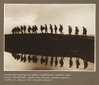 Frank Hurley - Image: Supports going up after battle to relieve the front trenches, note the three observation balloons above the bright cloud (3007981750)