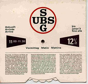 Promotional merchandise -  Swiss parking disk (early 1970s). Selected arrival time shows at the left window, departure at the right. Other side of disk is used for afternoon parking. Disk was a sales promotion for UBS bank.
