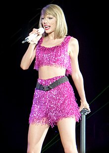 A photograph of Taylor Swift, as she looks away from the camera, performing live with a mic in her right hand.