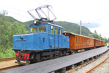 A small blue locomotive hauling three wooden passenger cars parked at a wooden platform
