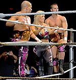 Photographie des catcheurs Tyson Kidd et David Hart Smith, accompagnés de Natalie Neidhart, alias Natalya.