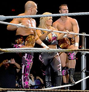 Tyson Kidd - The Hart Dynasty (from left to right) Kidd, Natalya, and David Hart Smith as the WWE Tag Team Champions in August 2010.
