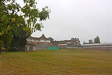 A grass playing field with buildings and tennis courts in the background