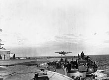 Black and white photograph of a single engined monoplane flying just above the deck of an aircraft carrier with its wheels extended. Two other aircraft are visible flying in the background of the photo.
