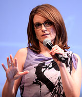 Tina Fey, a caucasian brown hair woman in her early 40s, wears a light purple paint splatter print dress. She wears dark-framed glasses, holds a microphone in her left hand, raises her right hand, and is in front of a light blue background.