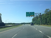 A four-lane asphalt road with a grassy median approaching an interchange. A green overhead sign reads MD 90 east Ocean City 1/4 mile west Salisbury exit only.