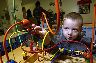Child care - A child playing with a toy in a daycare.