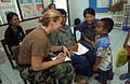 US Navy 070509-F-7806C-008 Hospital Corpsman 3rd Class Shauer, from Operational Support Hospital Unit (OSHU), talks to a local child during the distribution of prescription glasses in support of Cobra Gold 2007.jpg