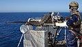 US Navy 070713-N-8014H-002 Gunner's Mate 2nd Class Eric Jensen fires a .50-caliber machine gun during weapons training aboard amphibious assault ship USS Boxer (LHD 4).jpg