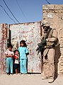 US Navy 070809-M-6412C-027 A Marine attached to Regimental Combat Team (RCT) 6 laughs with some Iraqi children outside of their house, during Operation Alljah.jpg