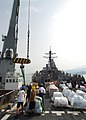 US Navy 080825-N-4044H-009 Sailors aboard the guided-missile destroyer USS McFaul (DDG 74) guide the crane cable onto the ship to transfer pallets of humanitarian assistance from the ship to the crane barge and then to the peop.jpg