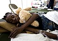 US Navy 100119-N-6266K-158 A young Haitian girl holds her teddy bear while she sleeps after receiving medical treatment at Gheskio Field Hospital.jpg