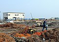 US Navy 110314-N-MU720-092 Mineman 2nd Class Cody Stone, from Phoenix, assigned to Naval Air Facility Misawa, walks through debris during a cleanup.jpg