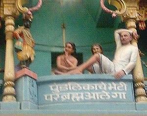 Pundalik - Image of a gopuram of a Pandharpur temple near Vithoba's central temple, depicting Vithoba (standing dark figure, left) waiting on the brick as Pundalik (centre) serves his parents.