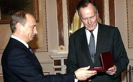 "Bush (right) with Russian president Vladimir Putin as he receives the Jubilee Medal ""60 Years of Victory in the Great Patriotic War 1941-1945"" from Putin in 2005. Vladimir Putin met with former U.S. President George Bush Sr.jpg"