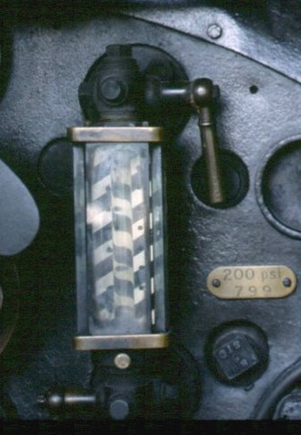 """Sight glass - Water gauge on a steam locomotive. Here the water is at the """"top nut"""", the maximum working level. Note the patterned backplate to help reading and toughened glass shroud."""