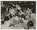 Young woman reading to girls at country camp, circa 1950 (7680417596).jpg