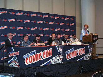 "IDW Publishing - The IDW ""Creator Visions"" panel at the 2013 New York Comic Con. From left to right: writers Sidney Friedfertig, Gary Gerani, Adadsam Knave, Dan Goldman, M. Zachary Sherman, Jeff Kline and Jason Enright. At the podium is IDW Vice President of Marketing Dirk Wood."