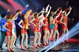 A group of six girls wearing red qipaos performing onstage