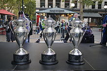 Three trophies placed in a line on a stage.