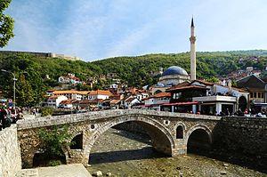 Die alte Steinbrücke umspannt die Bistrica. Im Hintergrund die Sinan-Pascha-Moschee und links auf dem Berg die Festung von Prizren