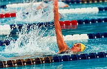 A woman swims the backstroke between two lanes in a swimming pool.