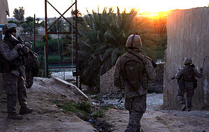 Three Marines patrolling through an Iraqi town near a river as the sun sets.